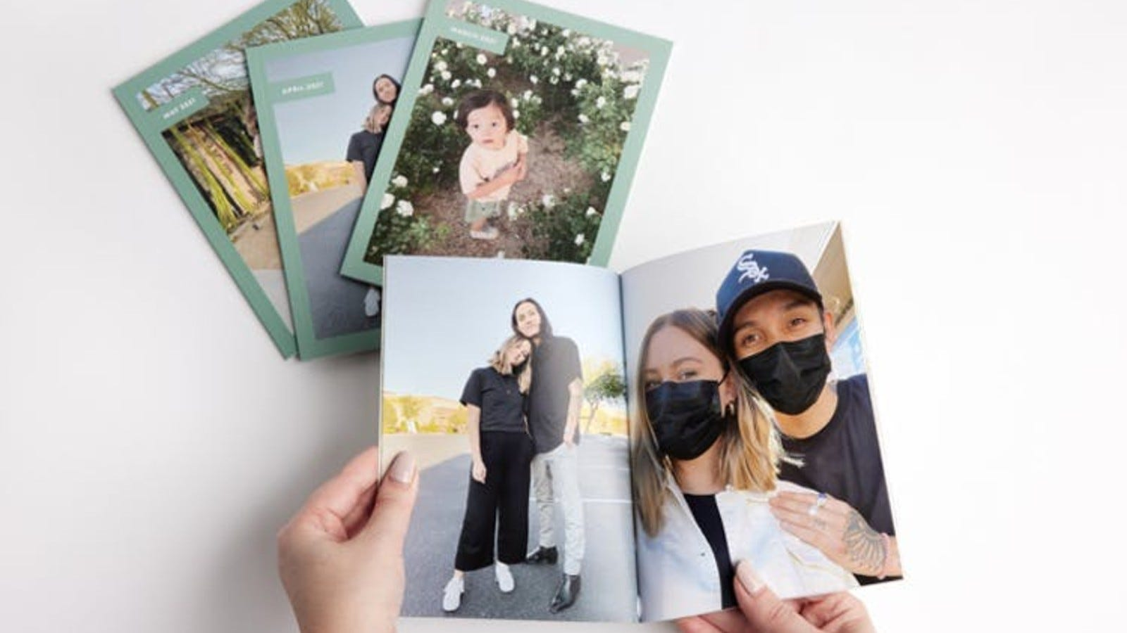 someone's hands flipping through a photobook filled with personal photos
