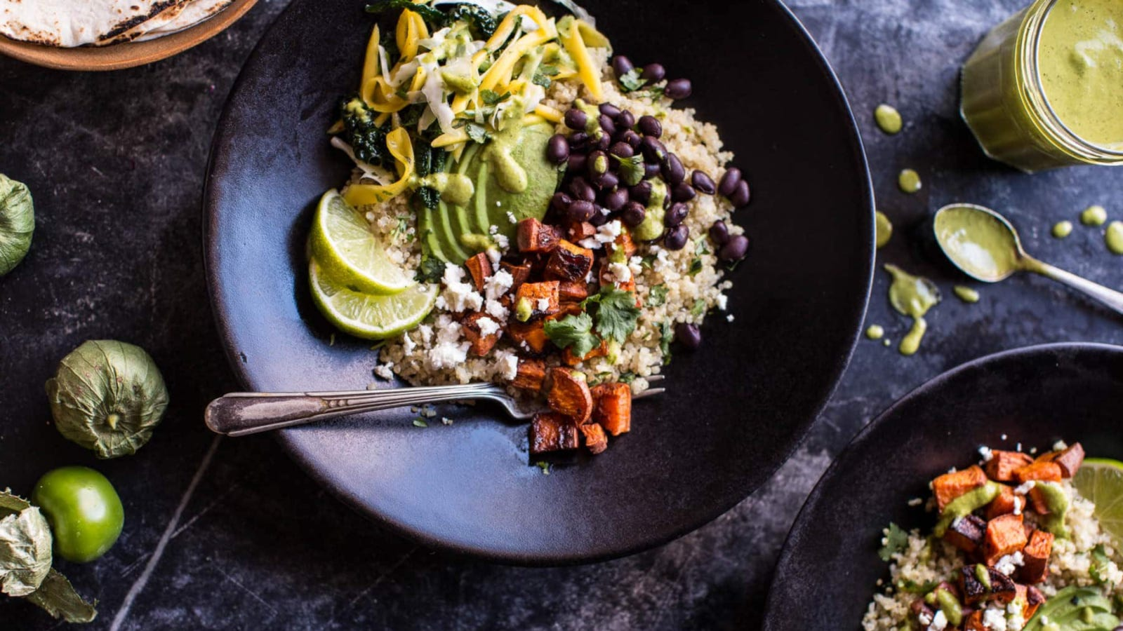 A black bowl filled with quinoa, roasted sweet potatoes and black beans, a mango slaw and roasted tomatillo vinaigrette.