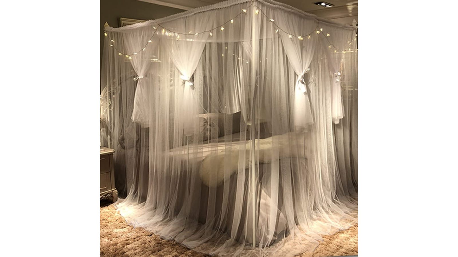 A white canopy draped over a square canopy bed frame with some sections tied with ribbon.