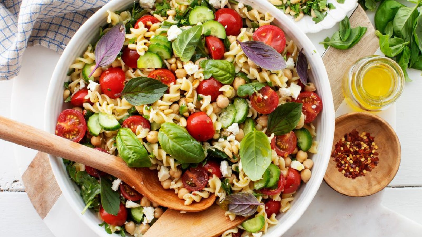 A large bowl of pasta salad filled with feta cheese, cucumbers, tomatoes, basil and more.