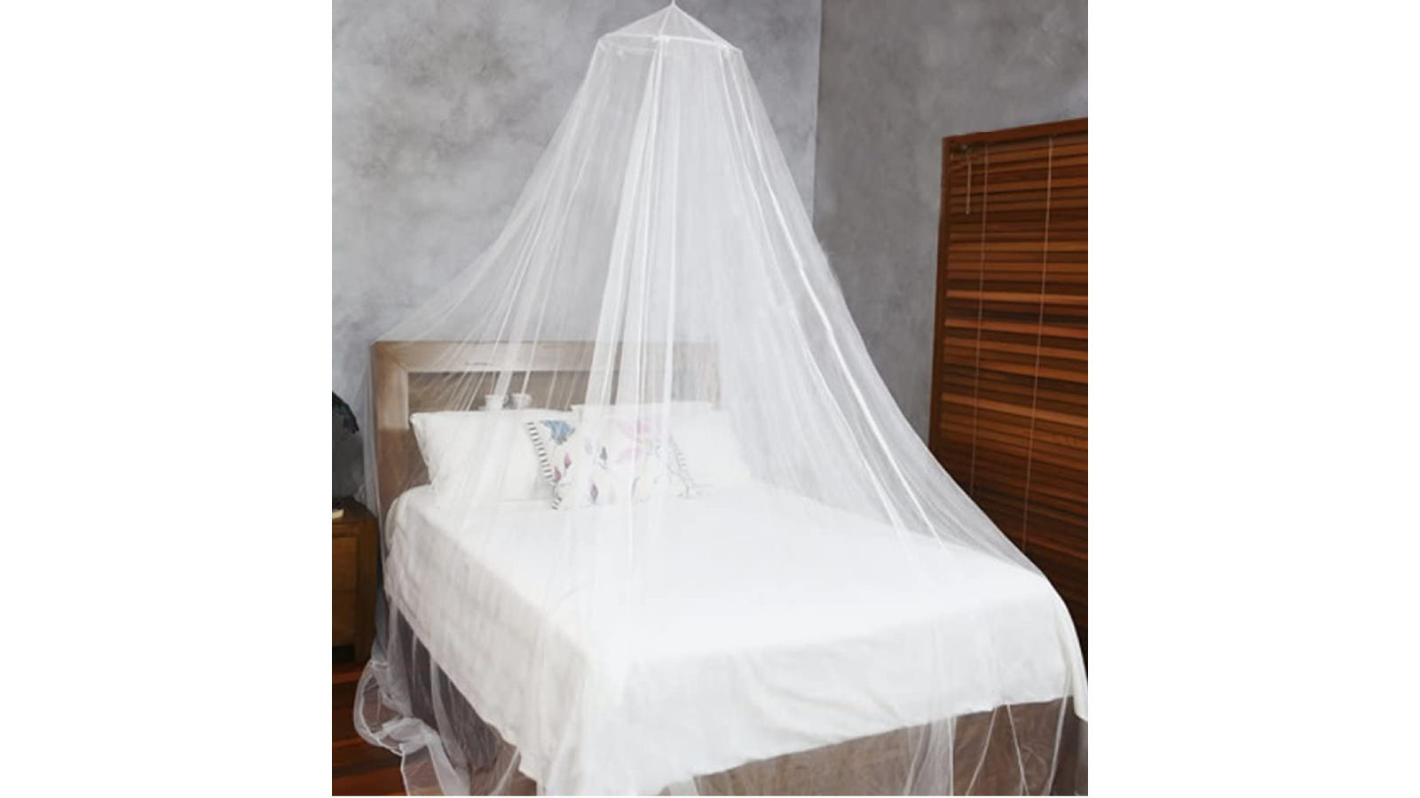 A white canopy with a round base hanging over a white bed.