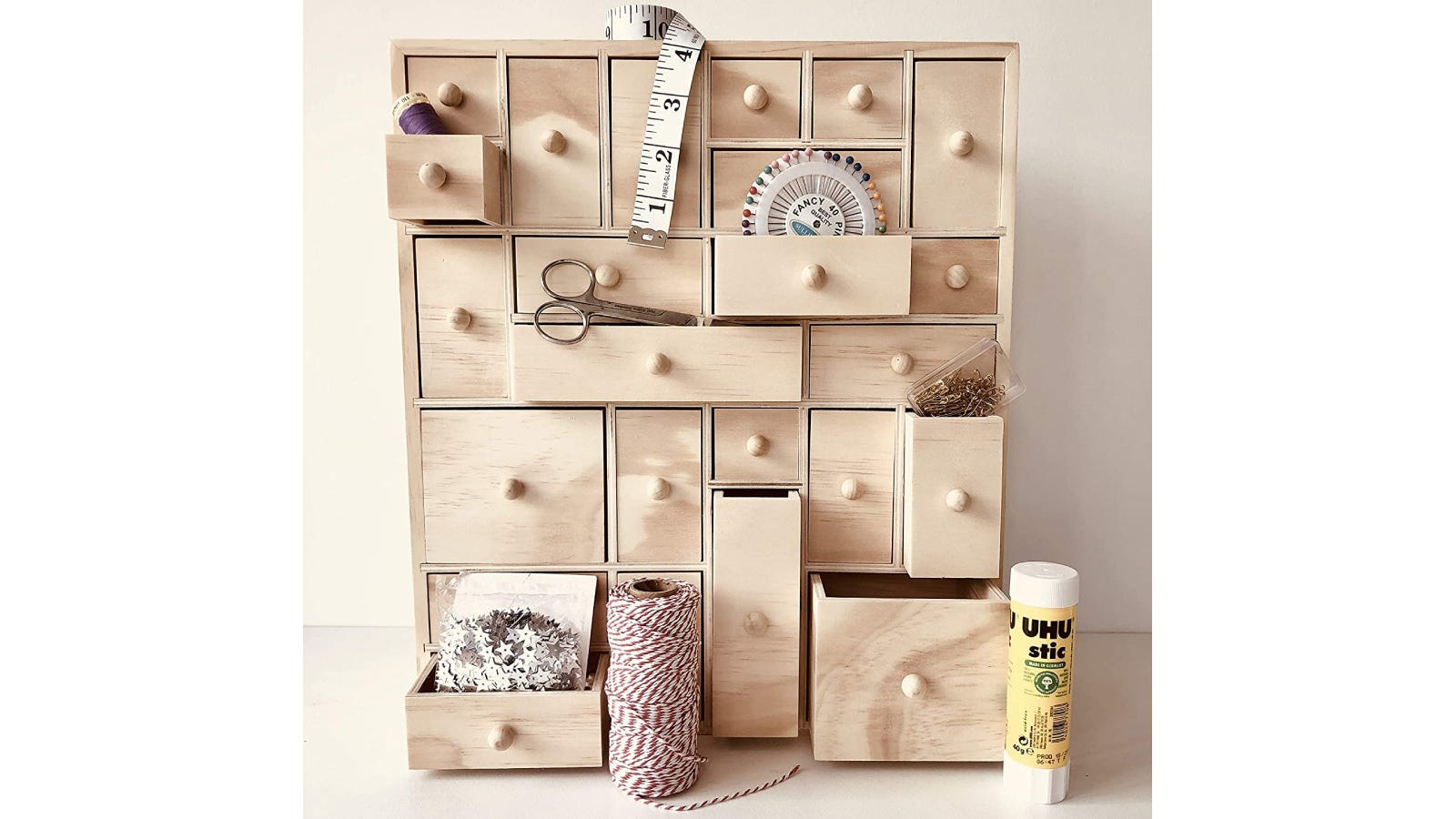A wooden storage organizer with some open drawers containing various crafting tools.