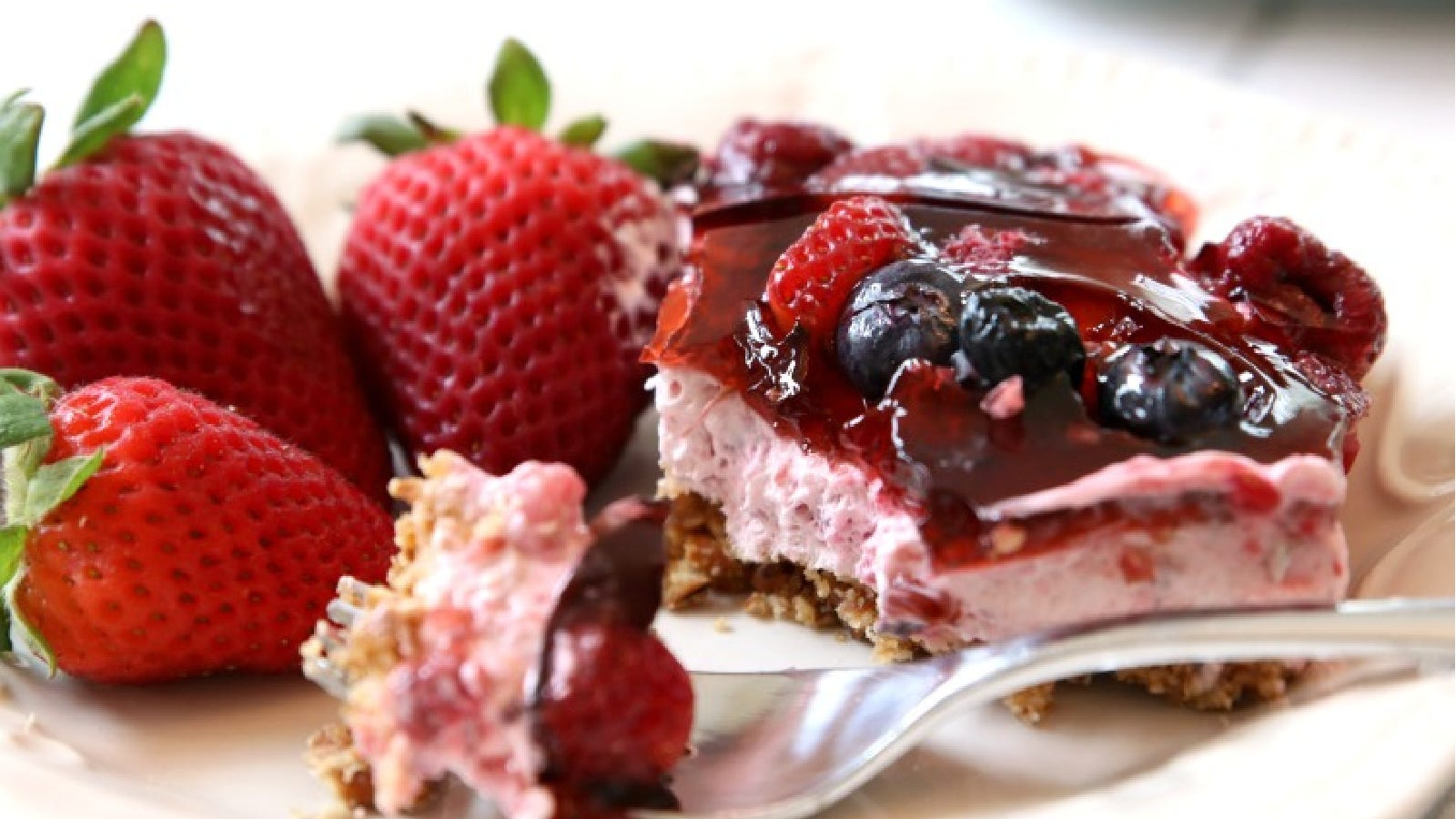 A square of berry jell-O pretzel salad topped with fresh berries and a side of strawberries.