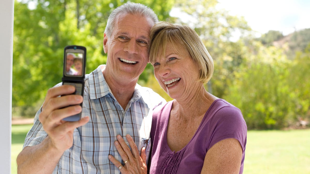 A senior couple on a weekend getaway take a photograph of themselves with a flip phone on a bright, sunny day.