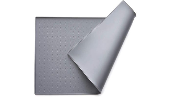 a gray silicone mat partially folded in half