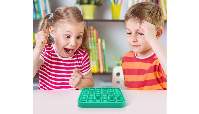 Boy and girl play with a green popping toy.