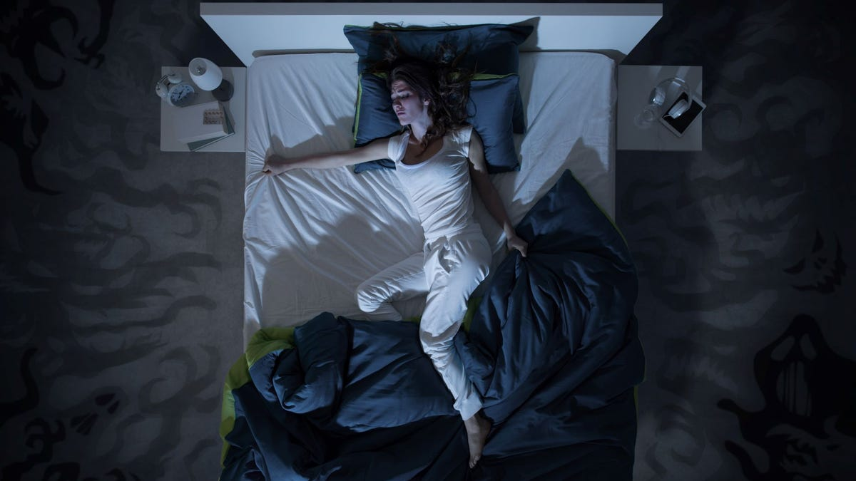 A woman in bed who's kicked the covers off.
