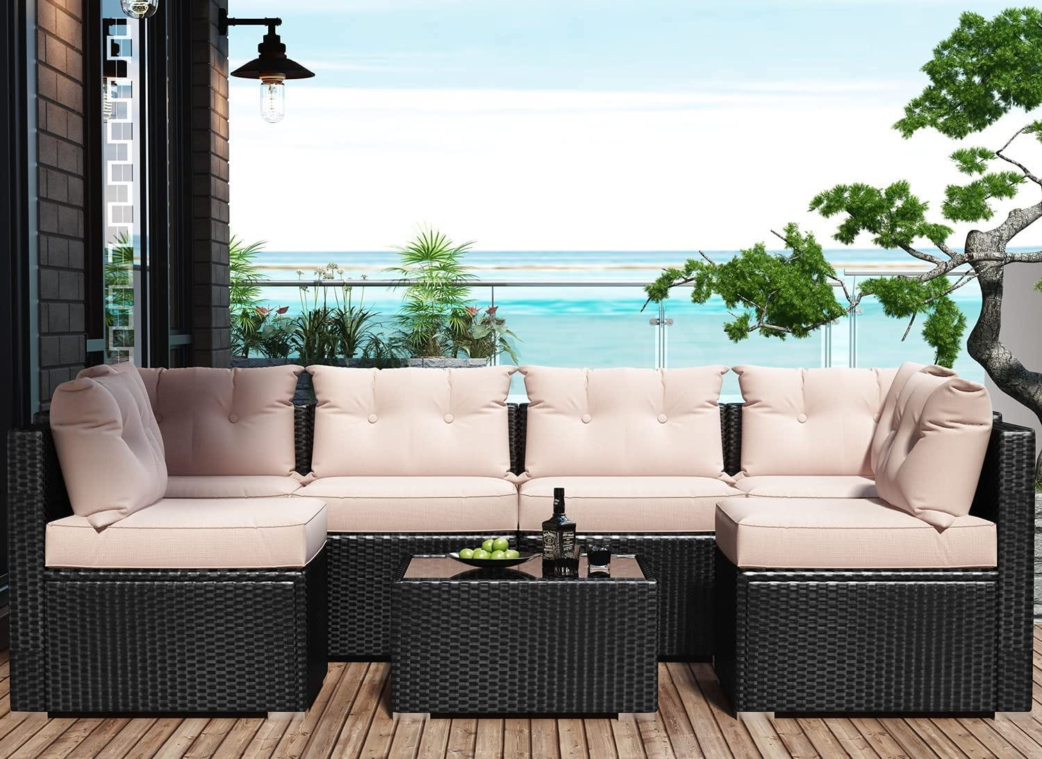 A beige and rattan outdoor sofa with tufted cushions, with the beach in the background