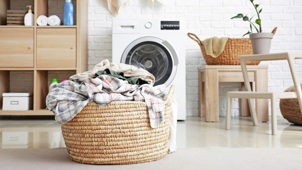 A laundry basket full of dirty clothes sitting in front of a washing machine.