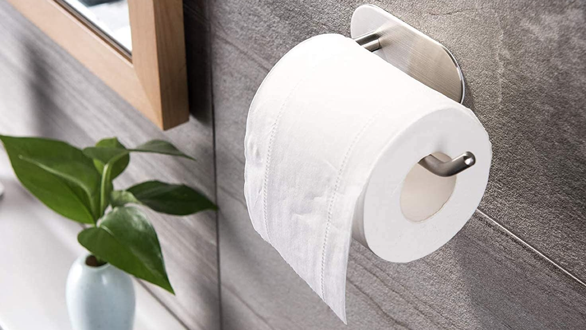 a chrome toiler paper holder with one open end, holding a half-used roll of toilet paper and mounted on a modern gray bathroom wall