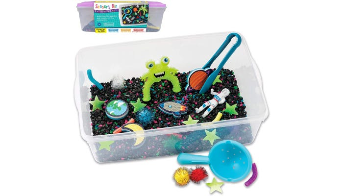 Bin filled with black sand and numerous outer-spaced themed toys.