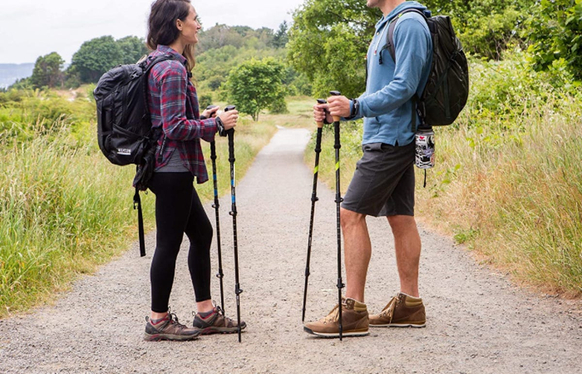 a young woman and young man standing on a hiking trail holding hiking poles, wearing backpacks, and having a conversation