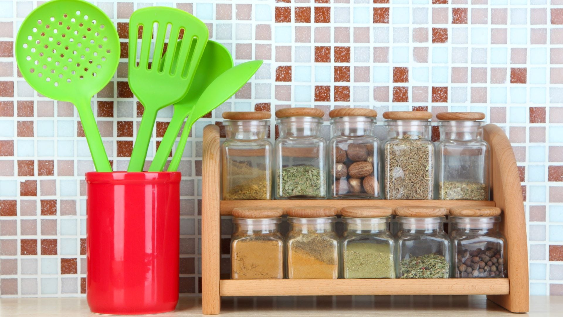 A container of spatulas and a spice rack on a counter.