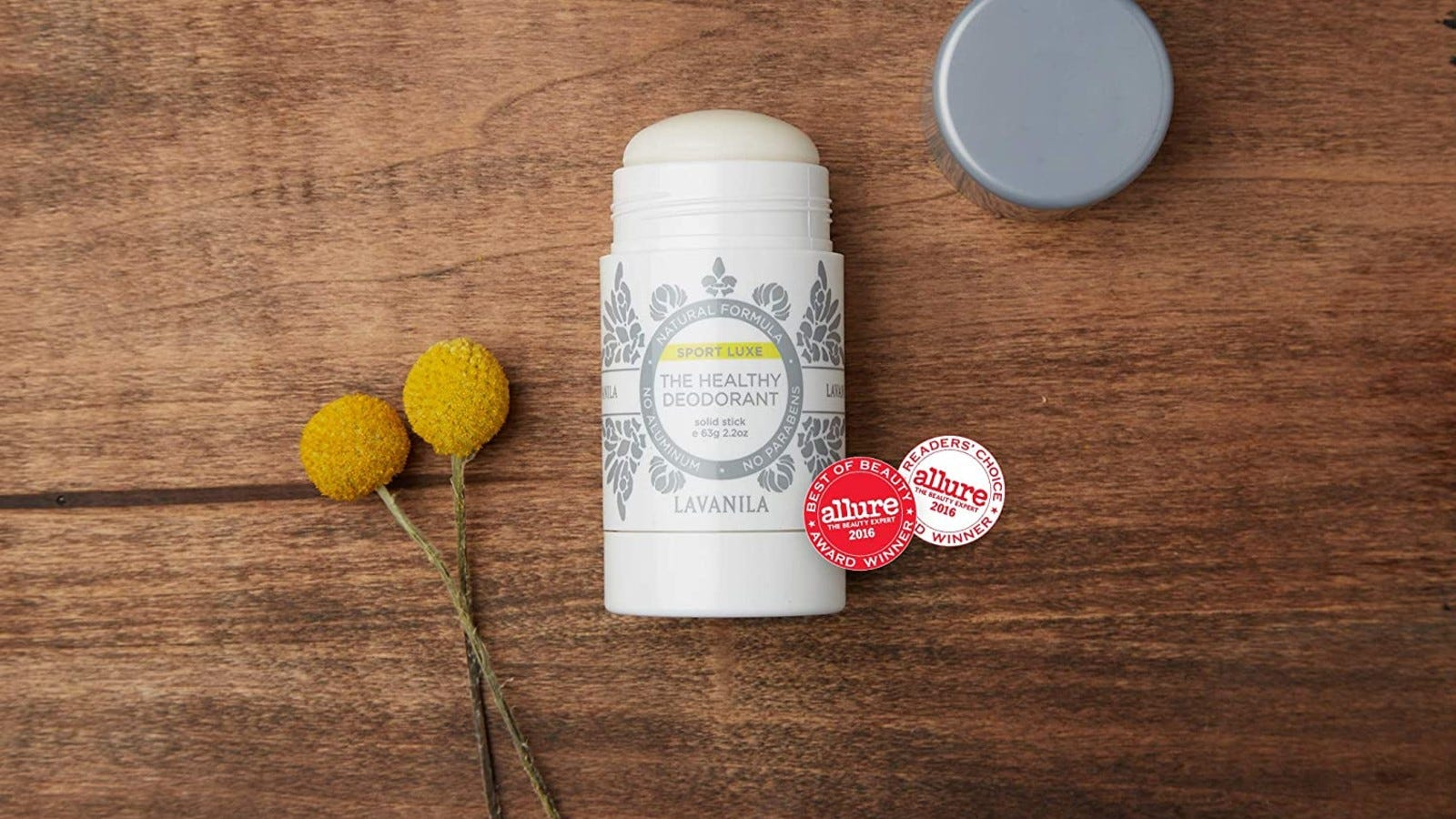 white Lavanila deodorant laying on a wood table with yellow flowers next to it