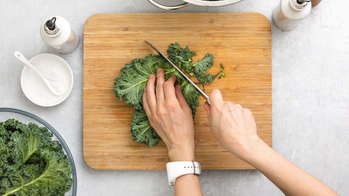 Someone chopping kale on a cutting board.