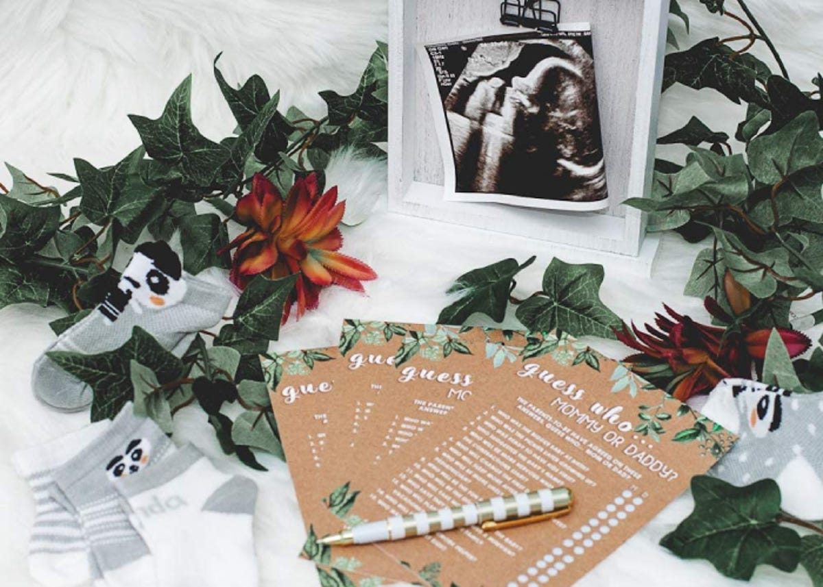 a stack of baby shower card games on a table with a baby sonogram and baby socks nearby