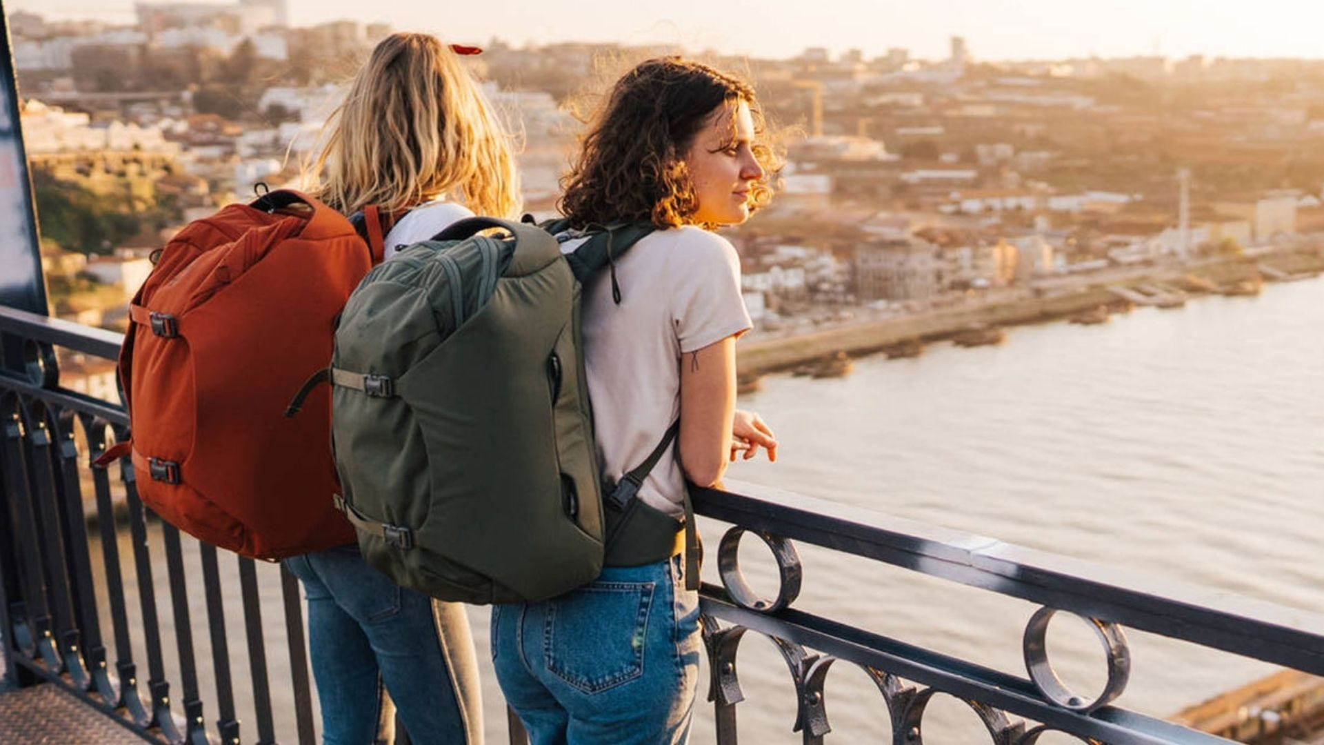 Two girls look over a bridge wearing travel baackpacks