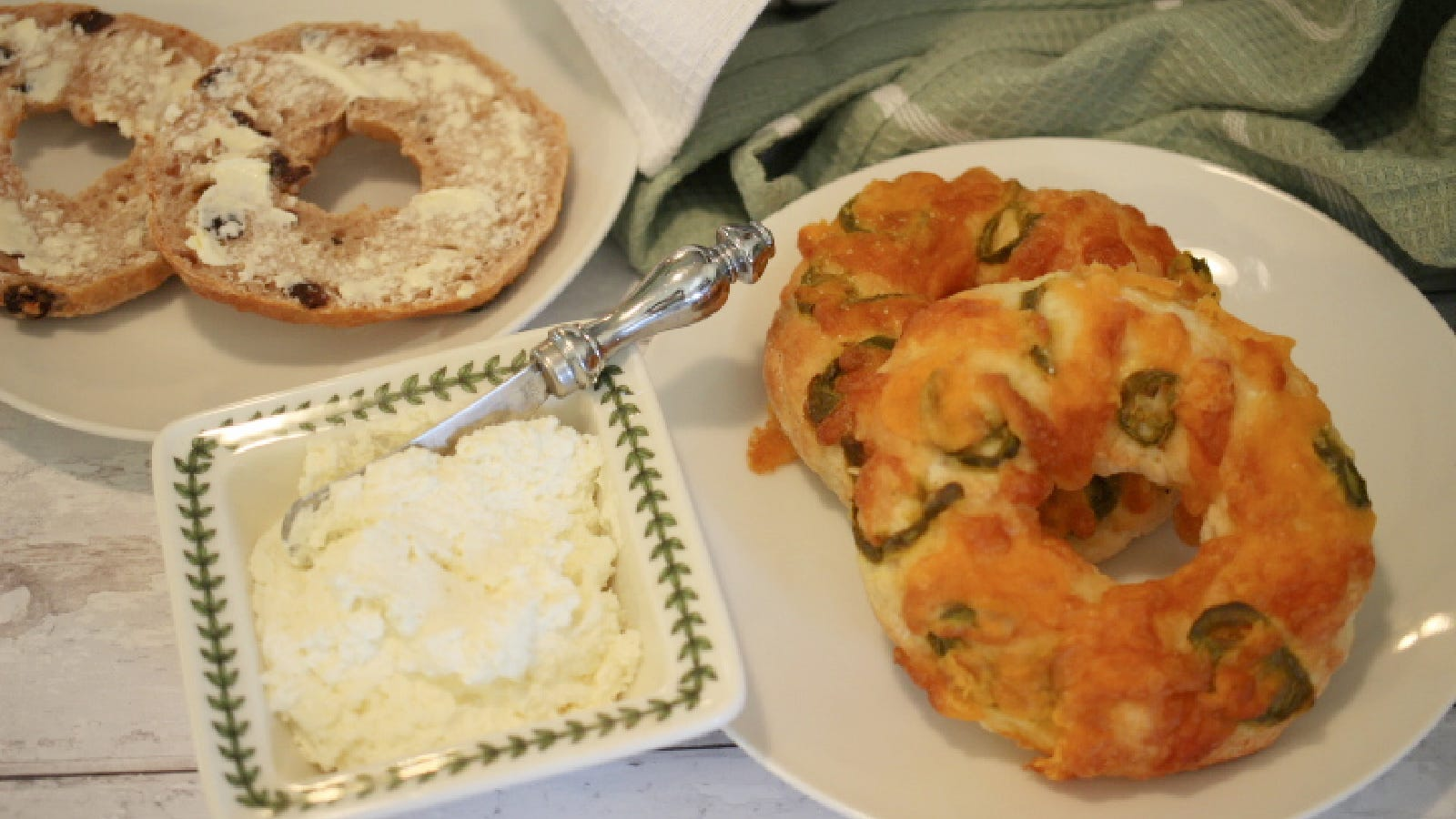 A jalapeno cheddar bagel next to a plate of cream cheese with a cinnamon raising bagel in in the background.