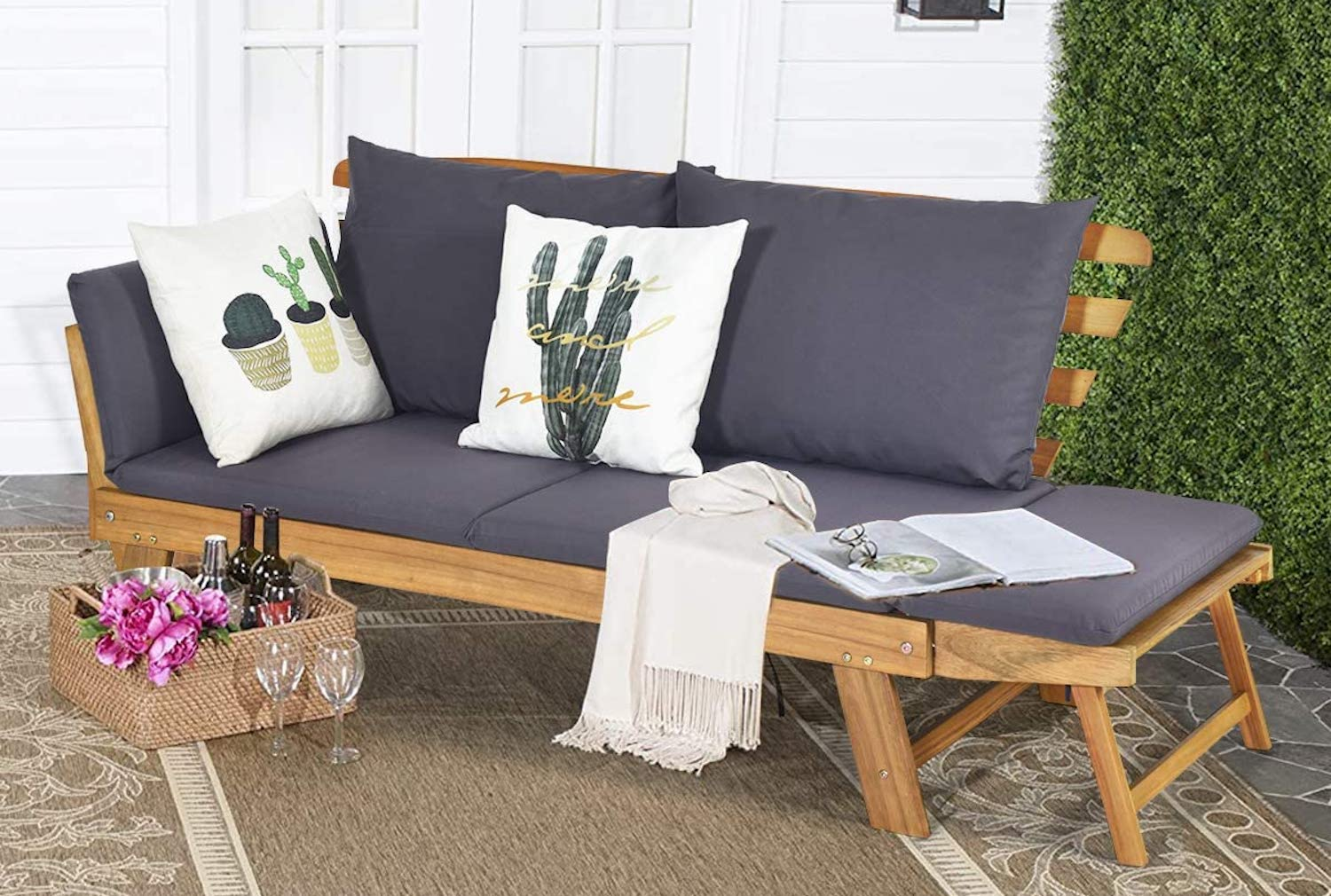 A gray patio sofa with a wood frame and white pillows on top