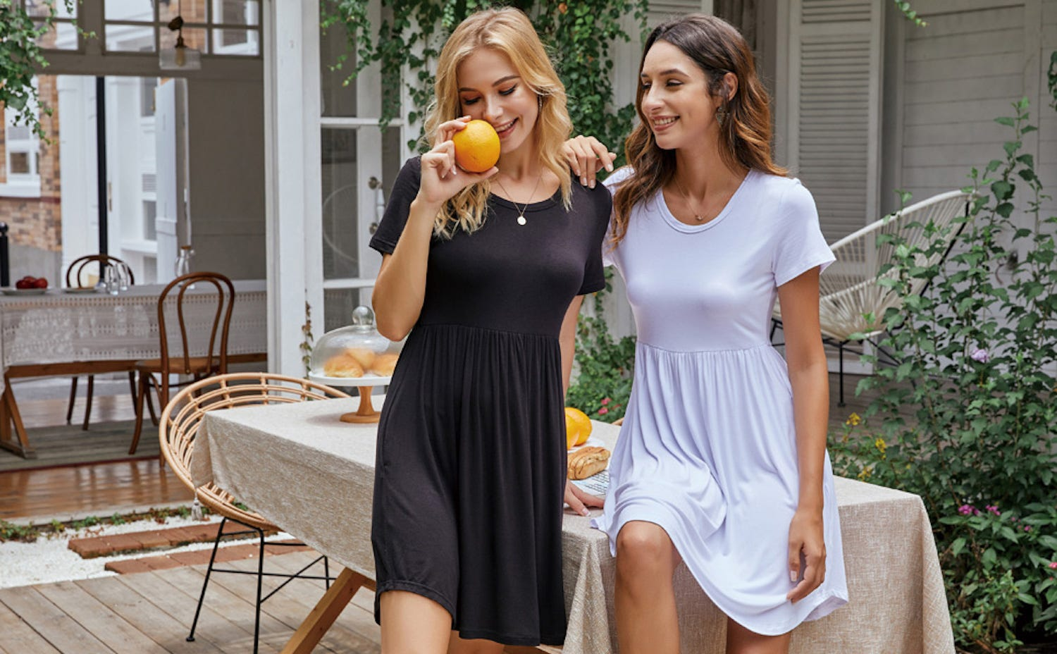 Two women on a patio: one in a black T-shirt dress, the other in a white T-shirt dress