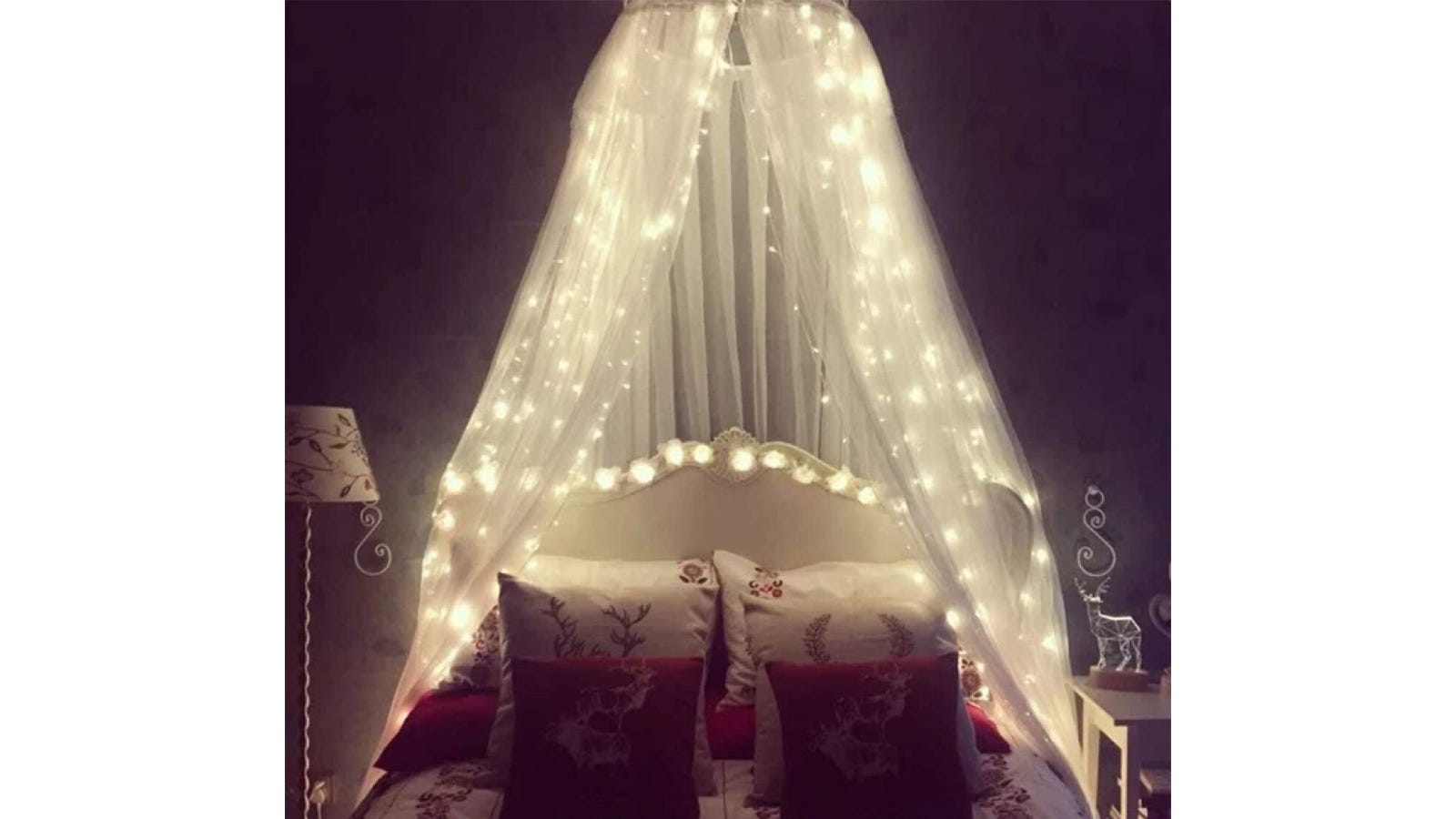 A white canopy with LED globe lights hanging open over a bed.