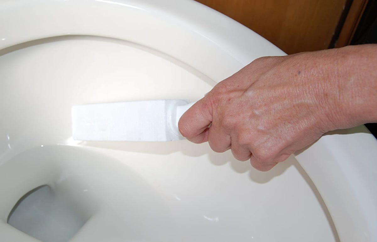 A man scrubbing the inside of his toilet with a pumice stone that has a handle