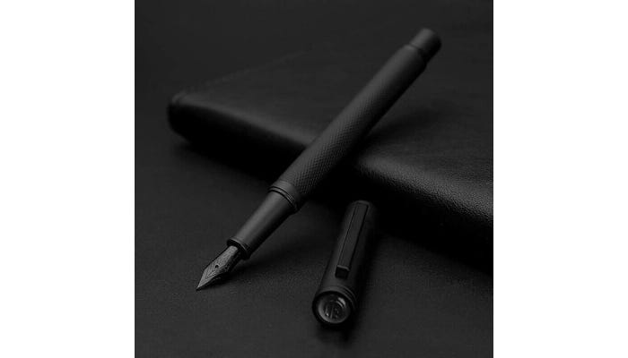 Matte black fountain pen with cap off to the side.