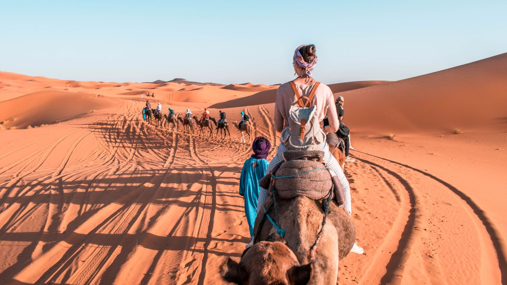 A long line of people riding camels in the Sahara Desert.