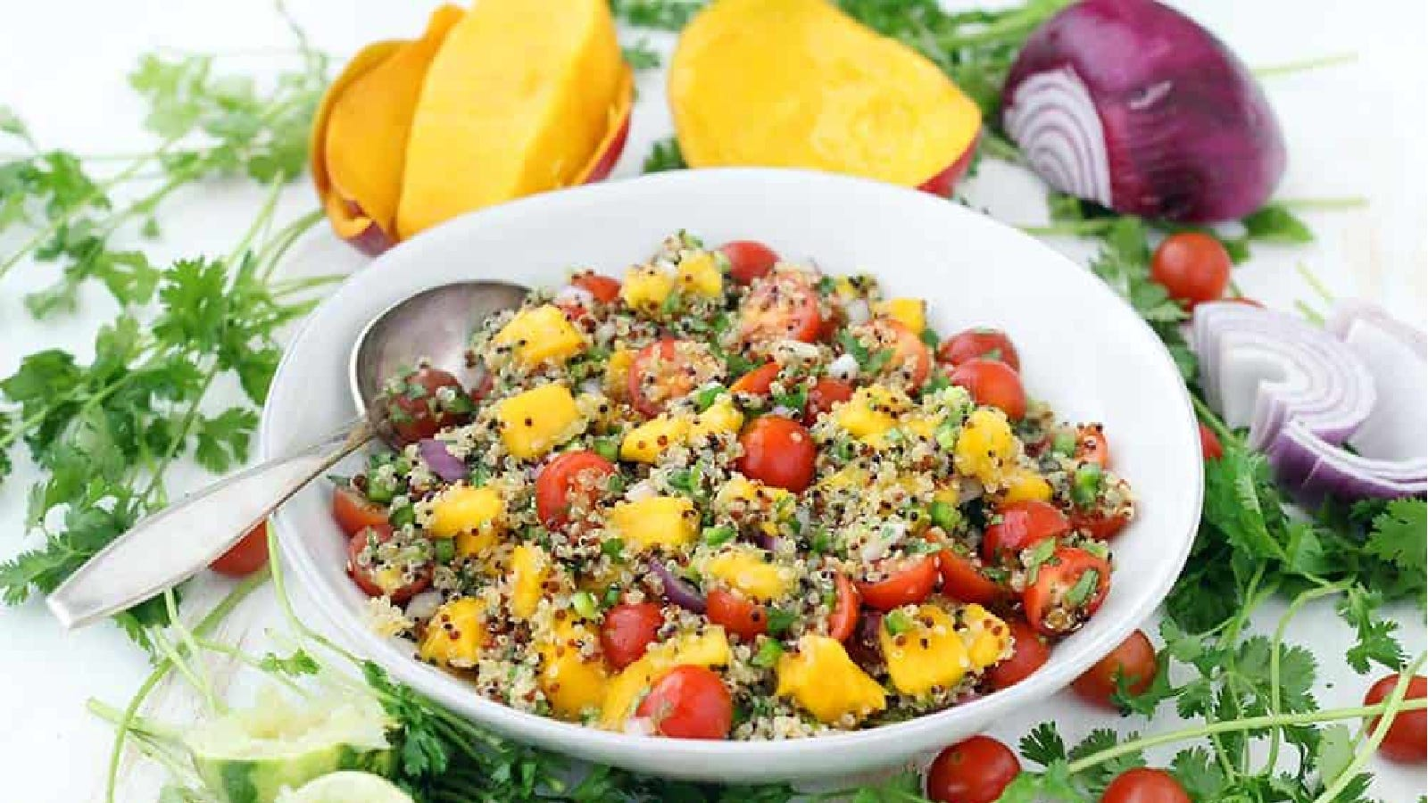 A shallow white bowl filled with mango quinoa salad, filled with tomatoes, jalapenos, red onion and mango.
