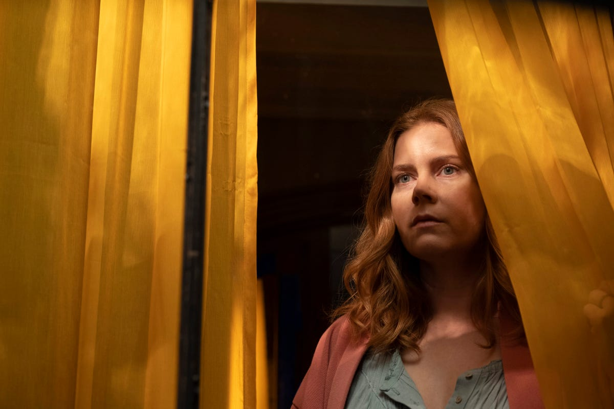 """Amy Adams looking out a window in a scene from """"The Woman in the Window."""""""