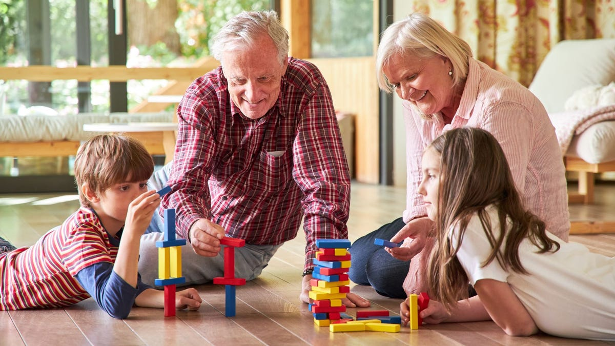 Grandparents and their grandchildren building with blocks on the floor.