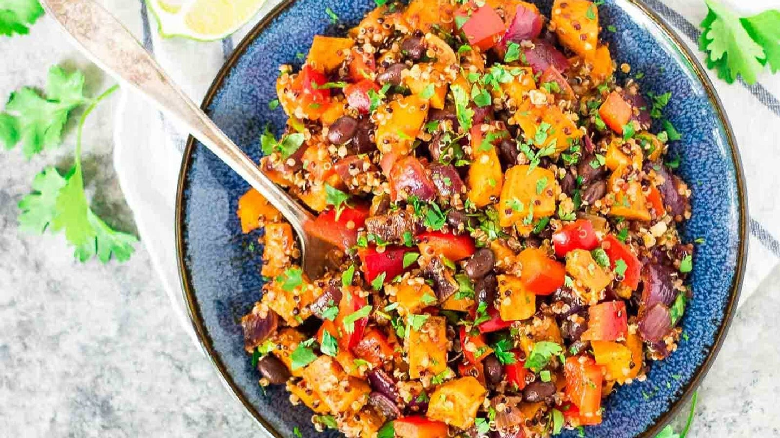 A rustic blue bowl filled with quinoa, sweet potatoes, and black beans.