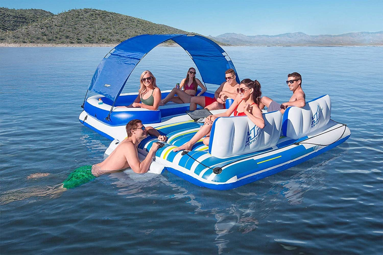 """A group of people lounging on an oversized floating """"island"""" float in a lake"""