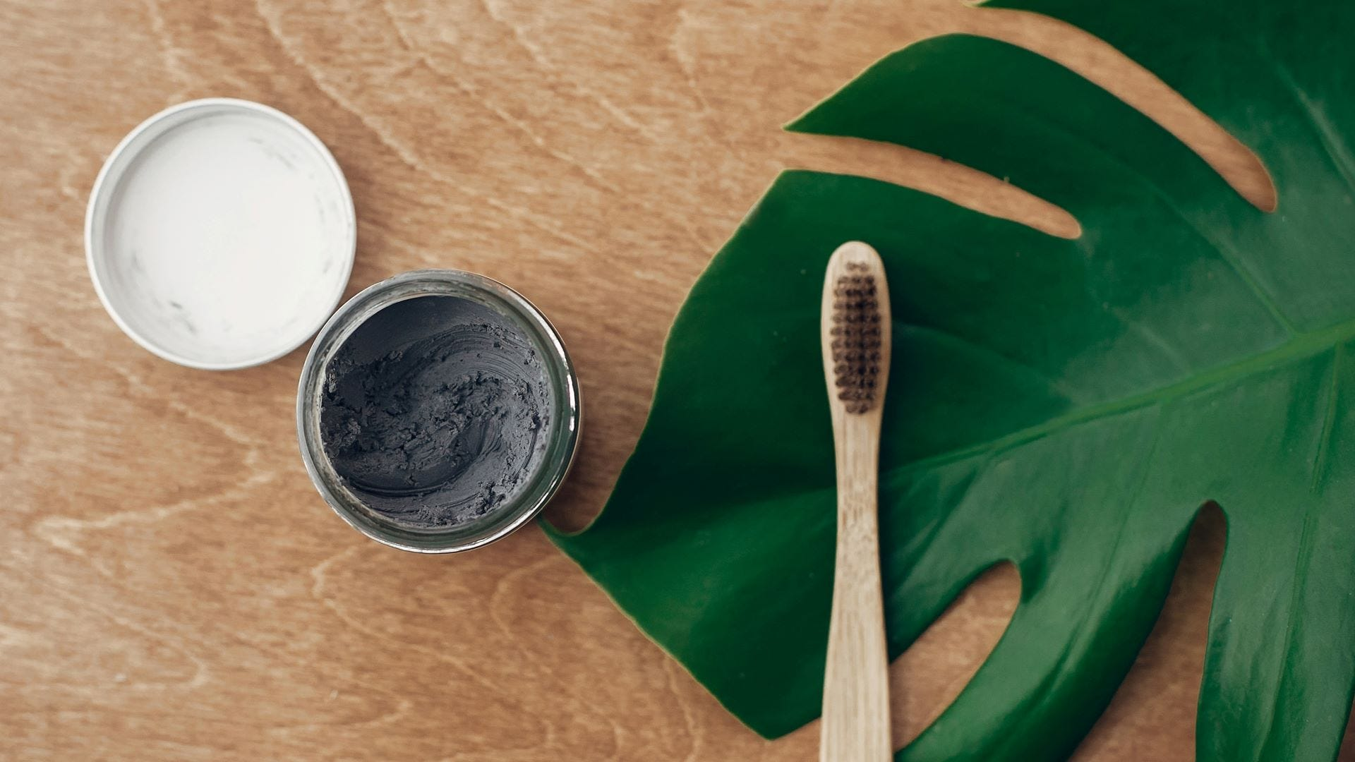 Natural activated charcoal toothpaste in glass jar next to a bamboo toothbrush.