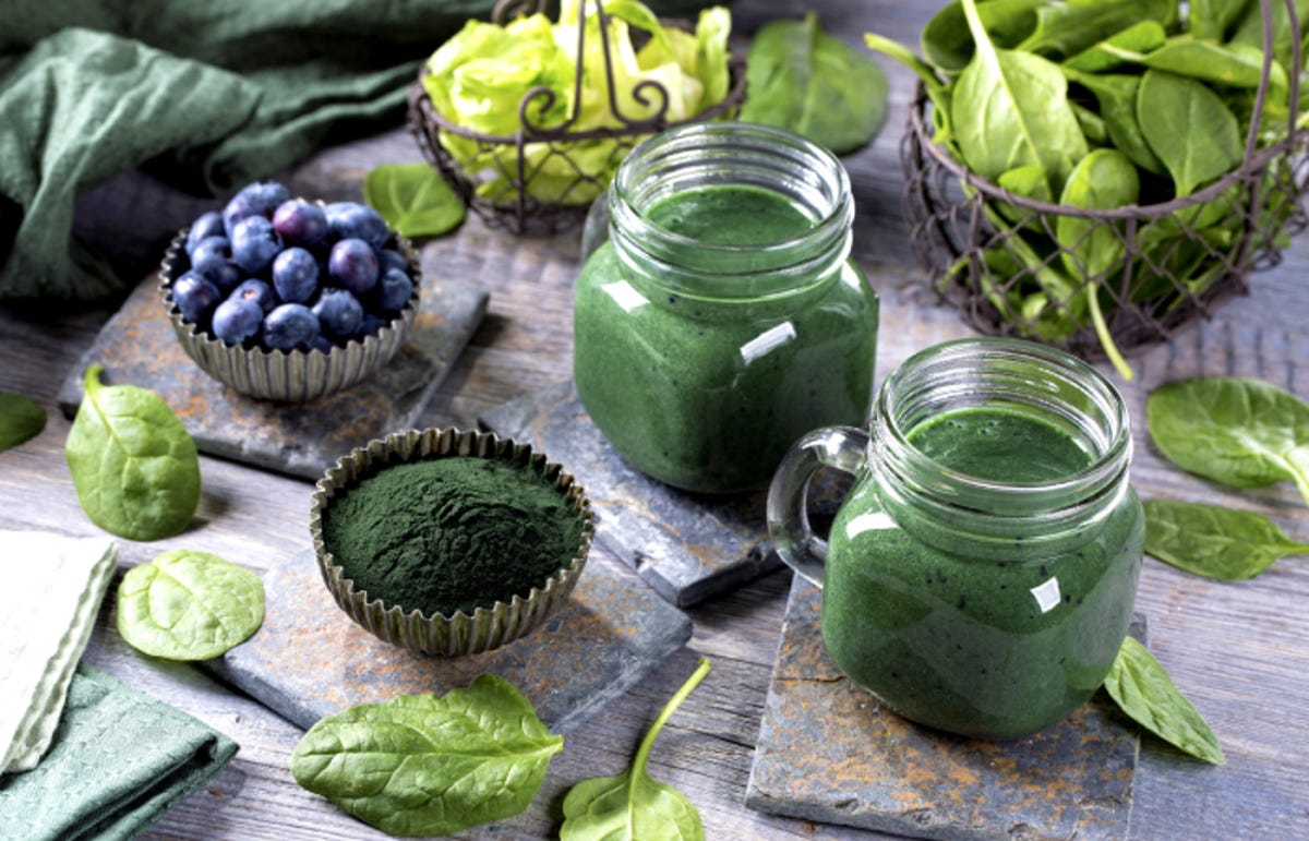 Green smoothies with spirulina powder,spinach, and blueberries on the table