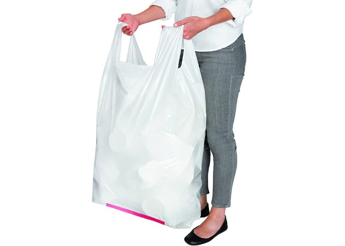 A woman in gray jeans holding full white trash bag by handles.