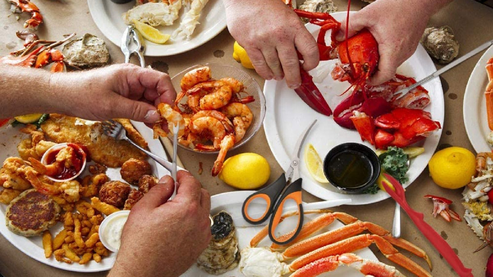 Two people enjoying a seafood feast, using the HIWARE seafood tool set.