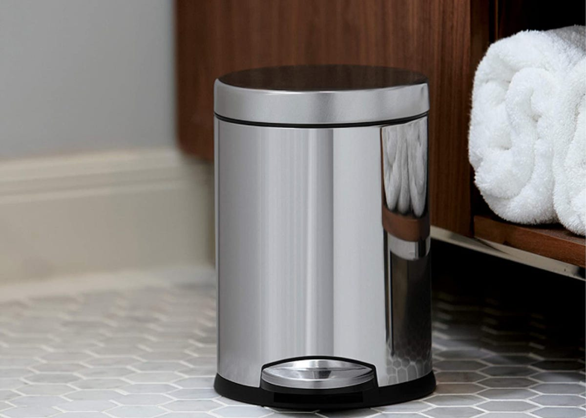 shiny silver small trashcan with lid and step to open it hands-free; in a bathroom