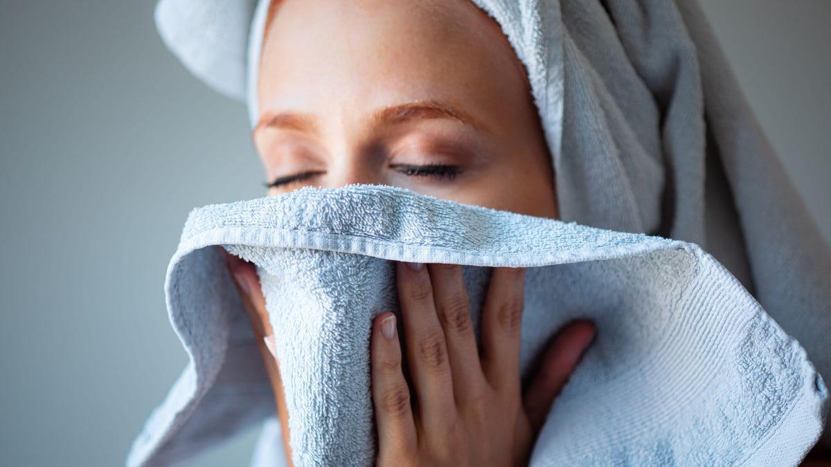 A woman drying her face with a towel.