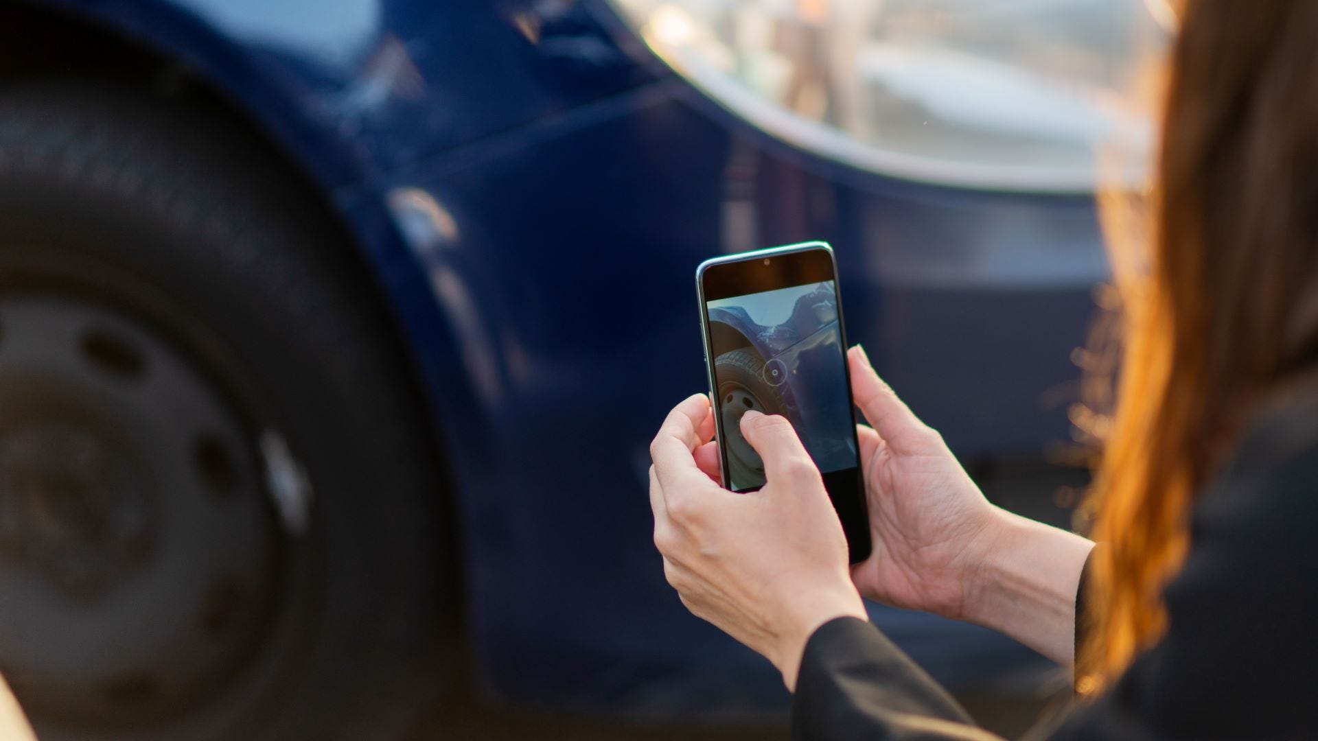 A woman taking a picture of a rental car with her phone.