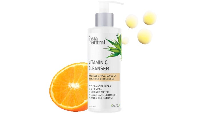 A bottle of InstaNatural Vitamin C facial cleanser is shown in front of a slide orange against a white background.