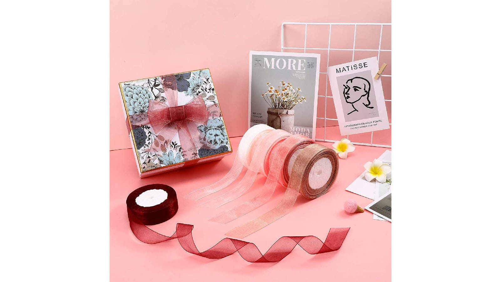 five dusty pink ribbons surrounded by magazine covers on a pink background