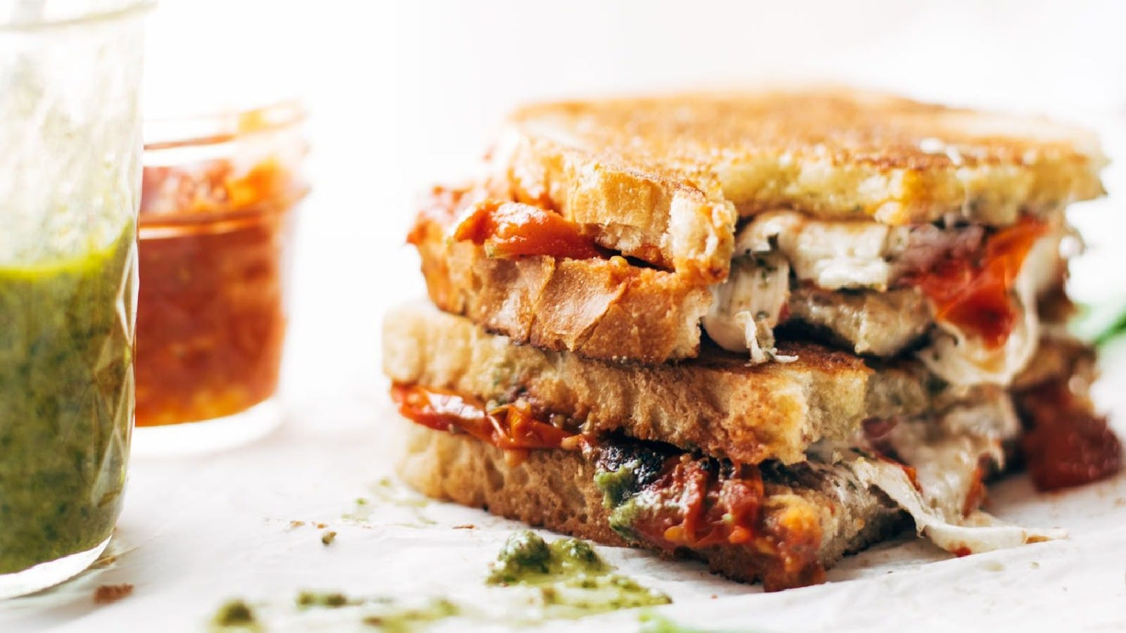 A stacked sandwich, filled with fresh mozzarella, pesto, and tomato garlic sauce.