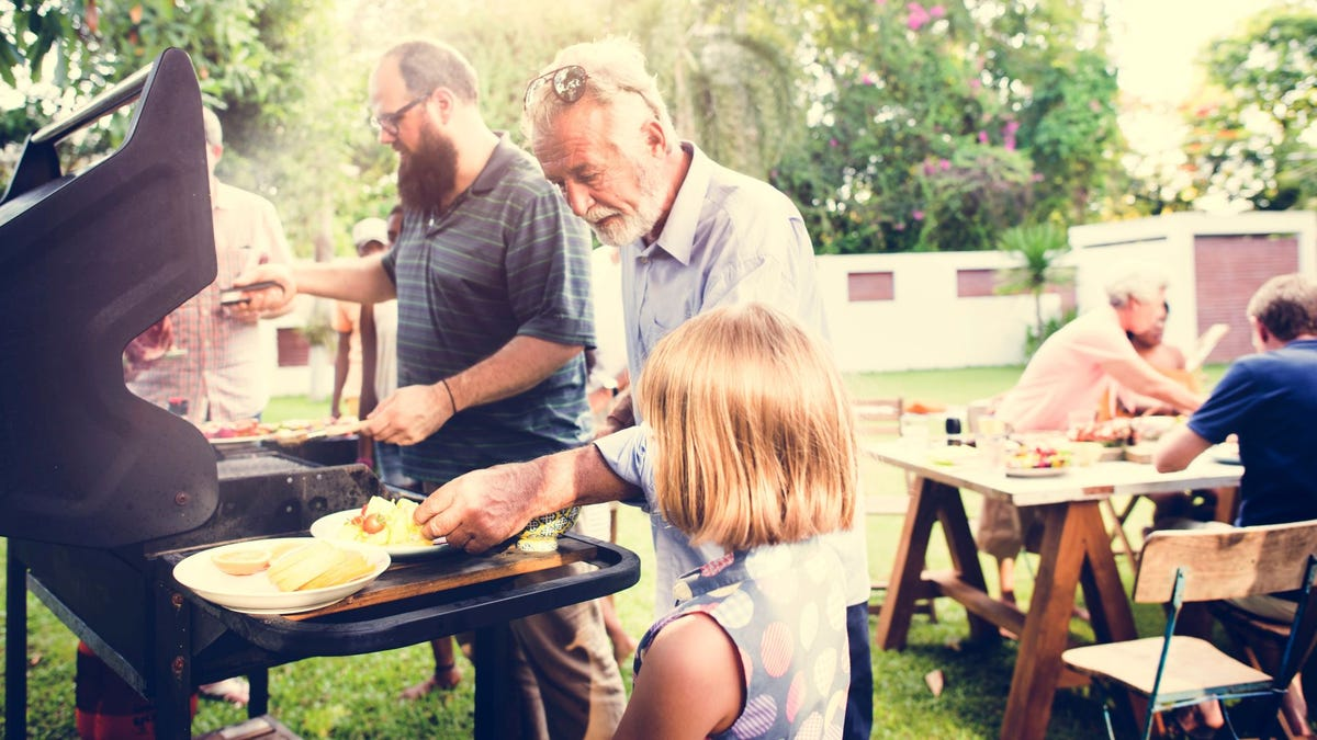 A family cooking out on a grill in a backyard.