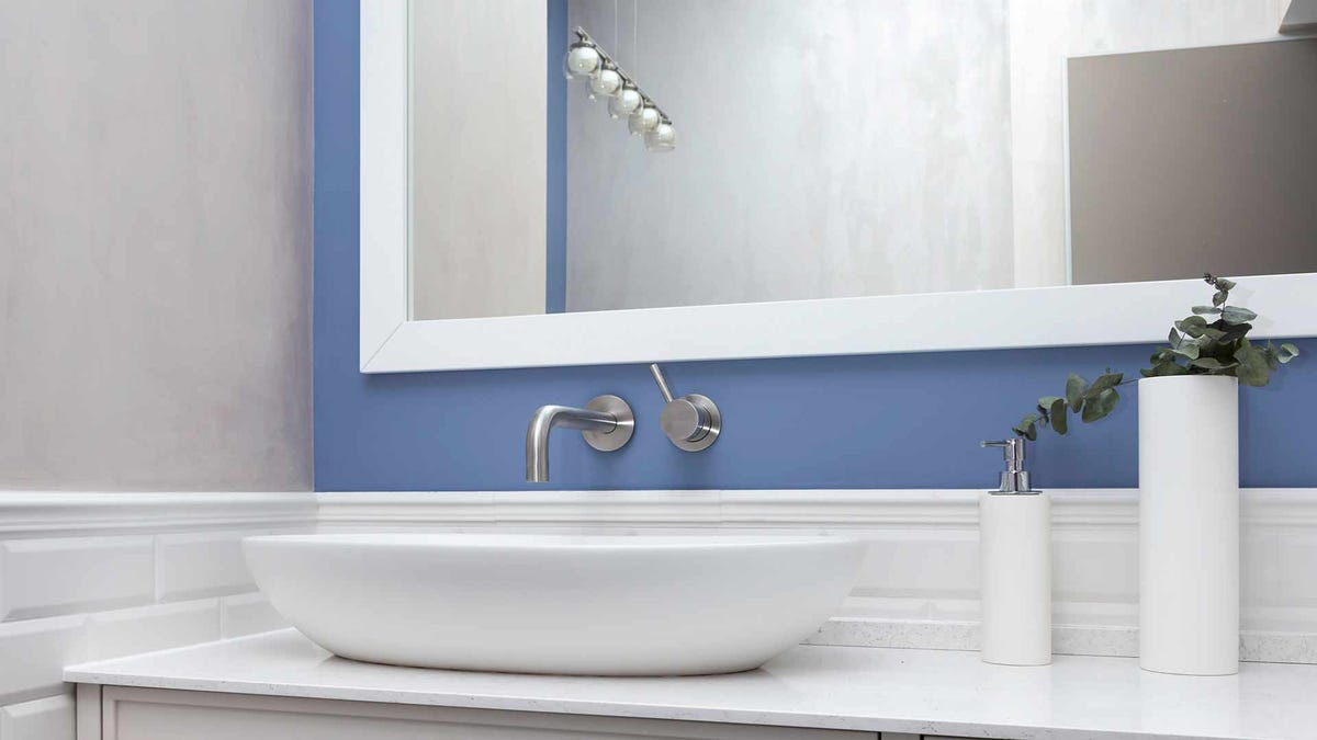 A modern white bathroom with a periwinkle blue accent wall.