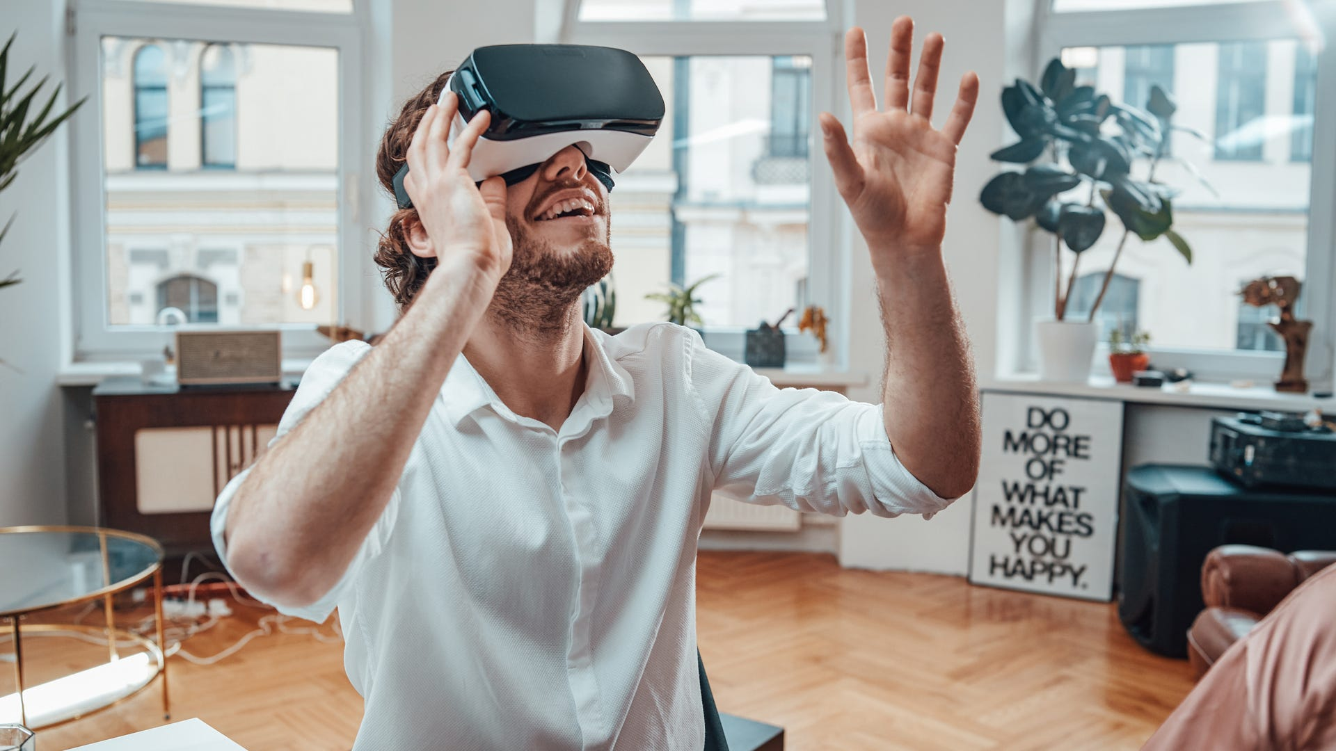 A man wears a VR headset and holds his hand out to reach for something he sees.