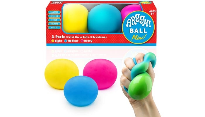 Packaging in background and a hand squeezing a green ball in foreground.