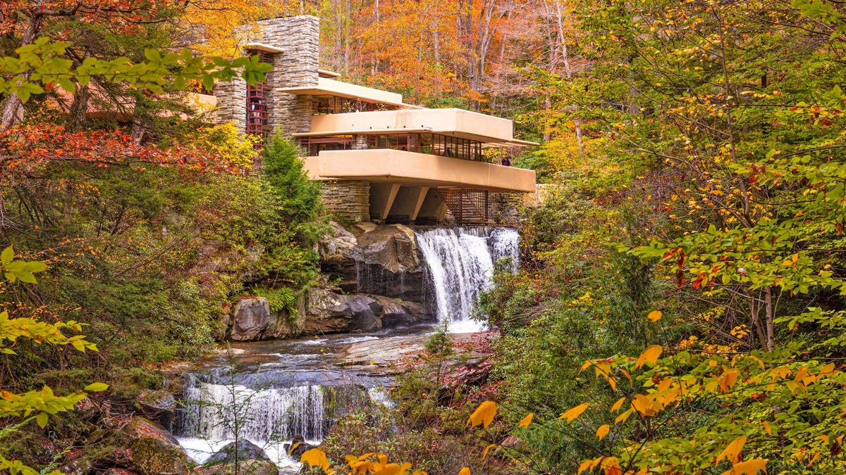 The waterfall at Fallingwater house designed by Frank Lloyd Wright, surrounded by trees in autumn.