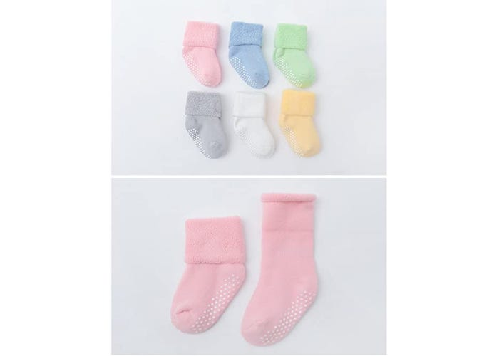 multiple pastel color baby socks on gray background