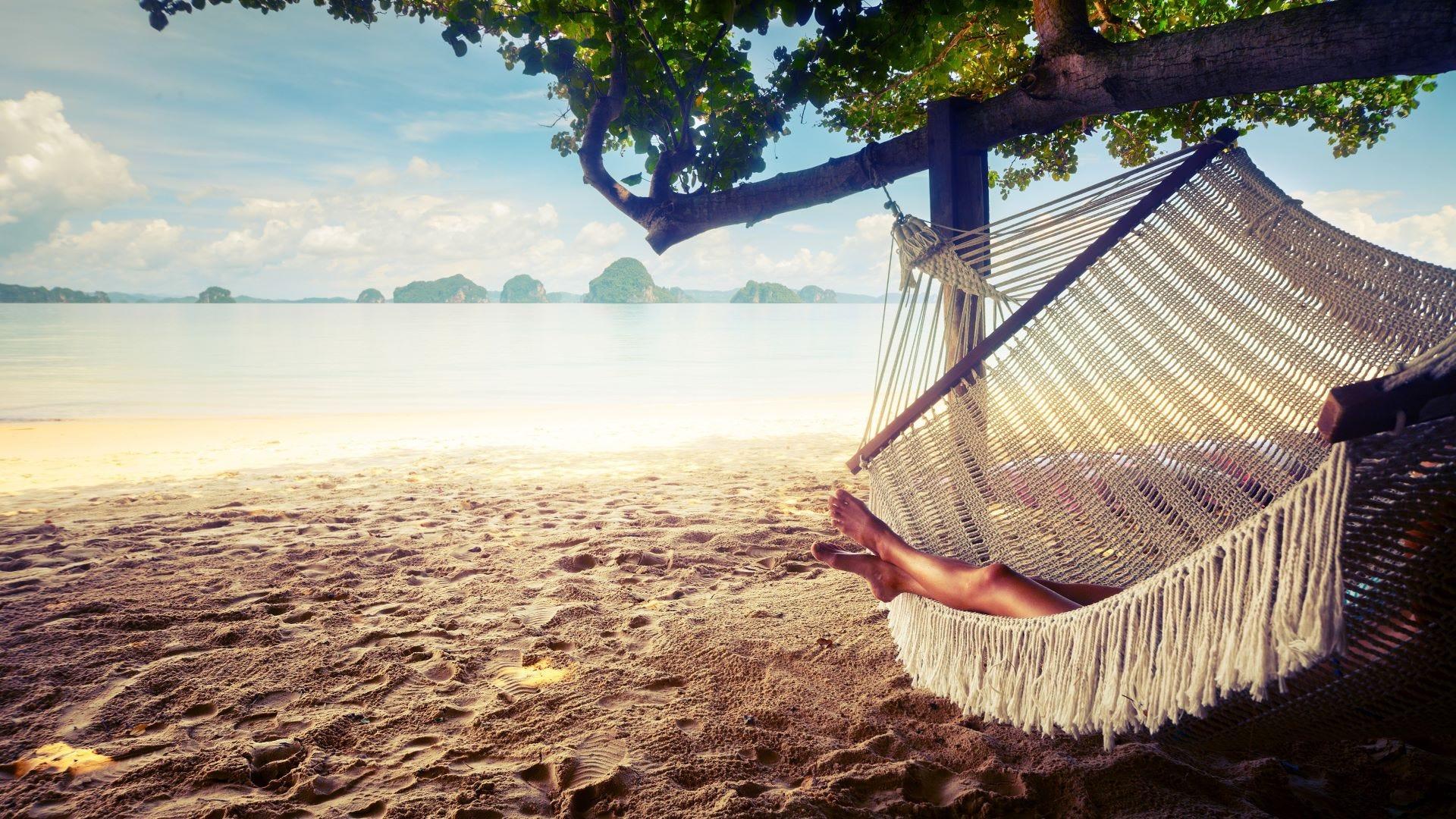 A woman lying in a hammock on the beach.